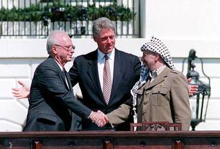 Yitzhak Rabin shakes hands with Yasser Arafat on the Oslo Accord, with President Bill Clinton, on 13 September 1993, in Washington D.C., US