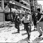 Yasser Arafat walks past destroyed buildings in Beirut