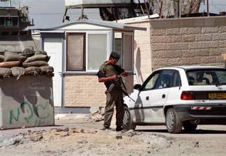 جندي إسرائيلي يفتش سيارة فلسطينية عند نقطة تفتيش Photo Shutterstock / اضغط للتكبير