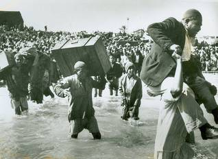 Palestinian refugees crossing a river Photo UNRWA Archive