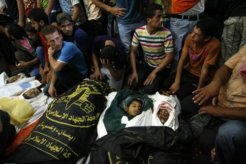 Palestinian relatives and friends mourn above the bodies of nine members of the Siam family, who were killed in an Israeli air strike that destroyed their house, 21 July 2014 / Photo Corbis