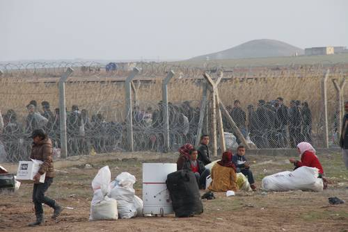 Syrians wait outside the Syrian-Turkish border gate near Akçakale, which Turkey closed after al-Qaeda militants took control of the Syrian side, January 2014 / Photo eyevine/HH