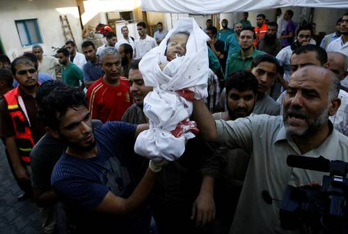 Relatives carry the body of a baby during the funeral of at least 9 members of the same al-Ghul family who died after their house was hit by an Israeli air strike in Rafah on 3 August 2014 / Photo Corbis