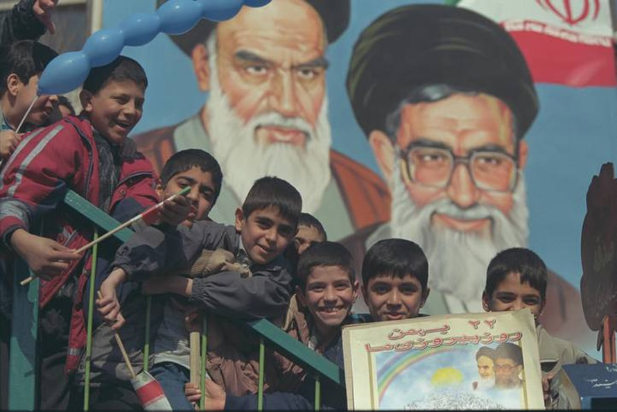 Iranian children at the celebration of the Islamic Revolution. Behind them are portraits of Khomeini and Khamenei. 20-10-2001 //Photo Corbis