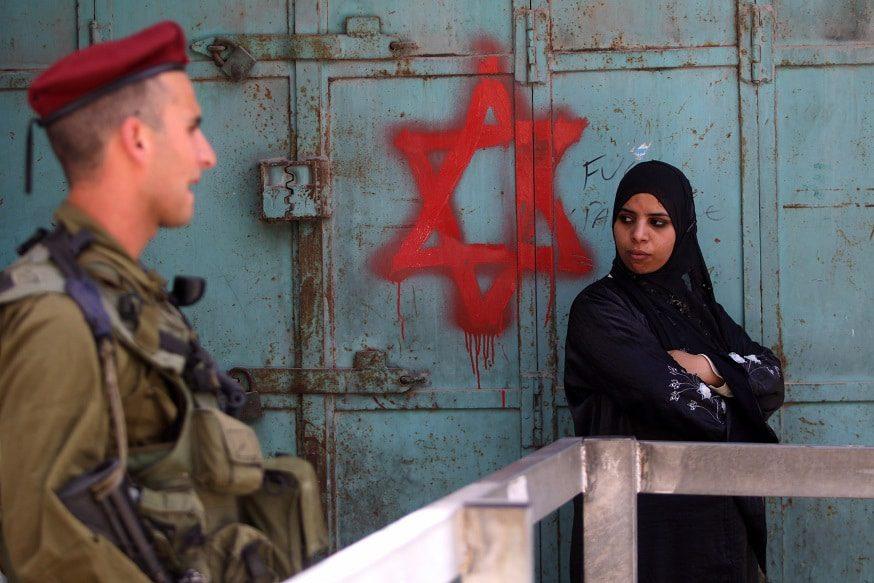 امرأة فسلطينية تنتظر في إحدى الحواجز العسكرية الإسرائيلية في الخليل /Photo New York Times