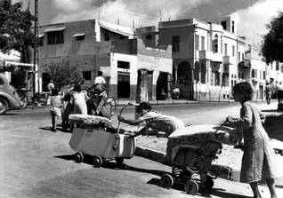 Barefoot and pushing their belongings in prams and carts, Palestinian families leave the Mediterranean coastal town of Jaffa, in 1948 reparation for palestinians