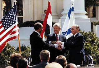 الرئيس أنور السادات والرئيس الأمريكي جيمي كارتر ورئيس الوزراء الإسرائيلي مناحيم بيغن يتصافحان أمام البيت الأبيض عام 1979 اضغط للتكبير