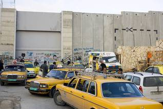 Taxis waiting at a checkpoint of the Wall near Bethlehem in the West Bank Photo HH