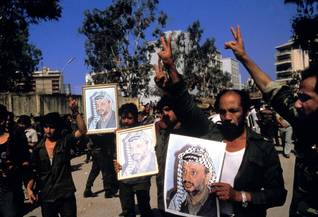 PLO members carrying images of their leader Arafat, as their organization is forced out of Beirut / Photo Magnum/HH