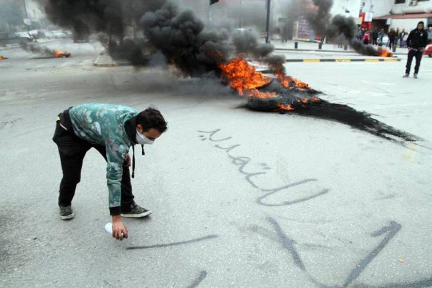 متظاهر ليبي يكتب شعاراً بينما يسد متظاهرون الشارع ويطالبون بلإفراج عن المتظاهرين المعتقلين,2 آذار/مارس 2014 / Photo Corbis