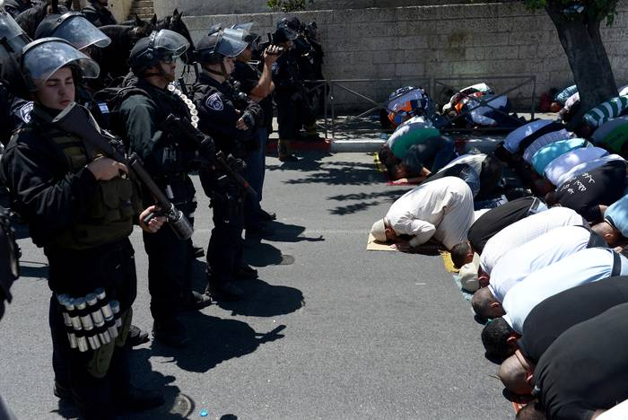 Muslims perform their Friday Prayer under Israeli security forces' control outside al-Aqsa Mosque on 1 August 2014 in Jerusalem / Photo Anadolu Agency