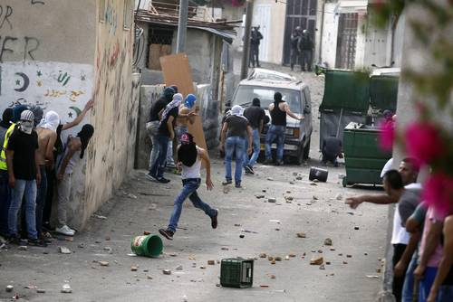 Palestinian protesters hurl stones during clashes with Israeli police in the East Jerusalem neighbourhood of Wadi Joz, 7 September 2014 Photo Polaris Images