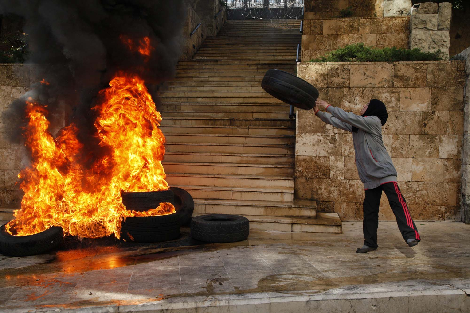 One of the relatives of the soldiers abducted by the Islamic State of Iraq and the Levant (ISIL) and Al-Nusra Front in the Arsal region of Lebanon close to Syrian border, throws tyre into fire during a protest in front of the Beirut Government Palace, Beirut, November 24, 2014. Wissam Fanash / Anadolu Agency