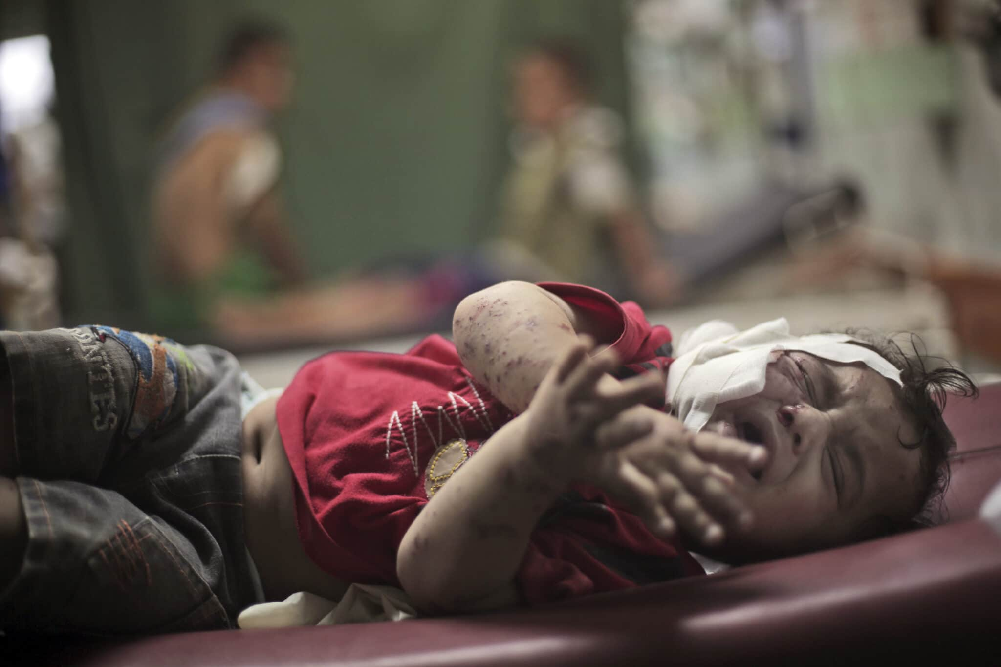 Beit Lahiya - July 30, 2014 - a Palestinian boy cries while receiving treatment for injuries caused by an Israeli strike at a U.N. school in Jebaliya refugee camp, northern Gaza Strip. A fierce debate is raging within Israel's military over the extent to which soldiers should be held legally accountable for their actions during Gaza war(AP Photo/Khalil Hamra, File)