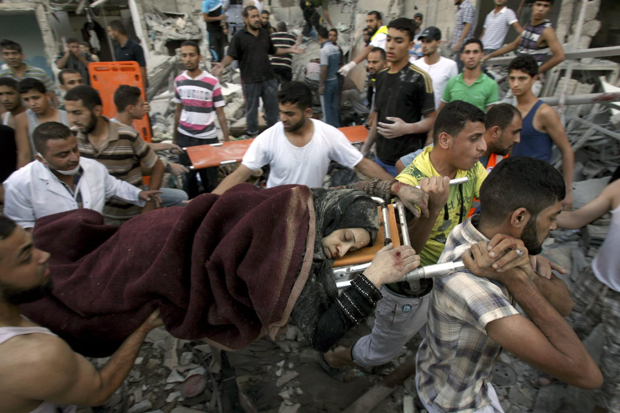 Men evacuate a survivor of an Israeli airstrike that hit the Al Ghoul family building in Rafah, southern Gaza Strip, killing and wounding many members of the family. A fierce debate is raging within Israel's military over the extent to which soldiers should be held legally accountable for their actions during last year's Gaza war. (AP Photo/Eyad Baba, File)