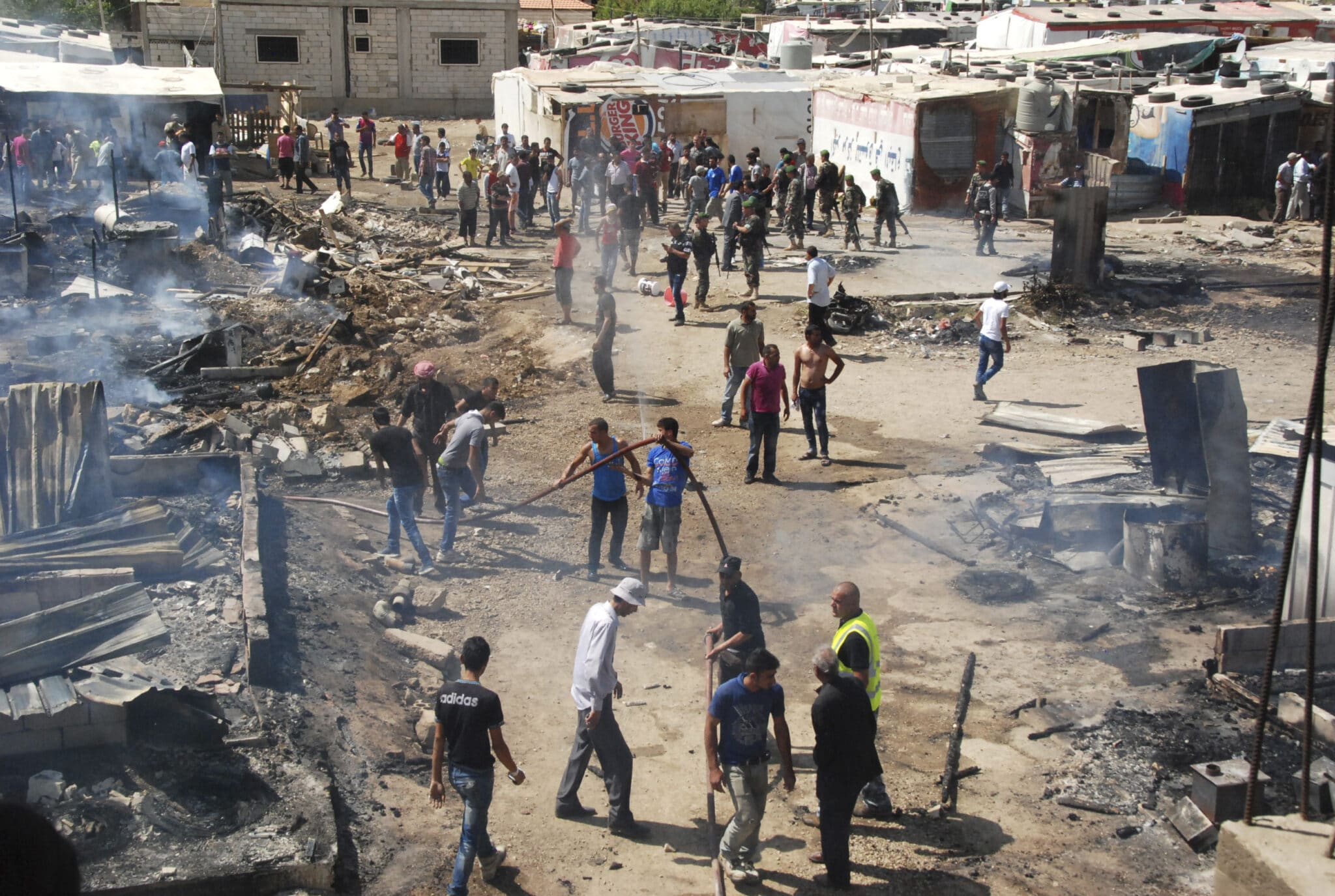 Syrian refugees estinguish a fire in a camp in Lebanon