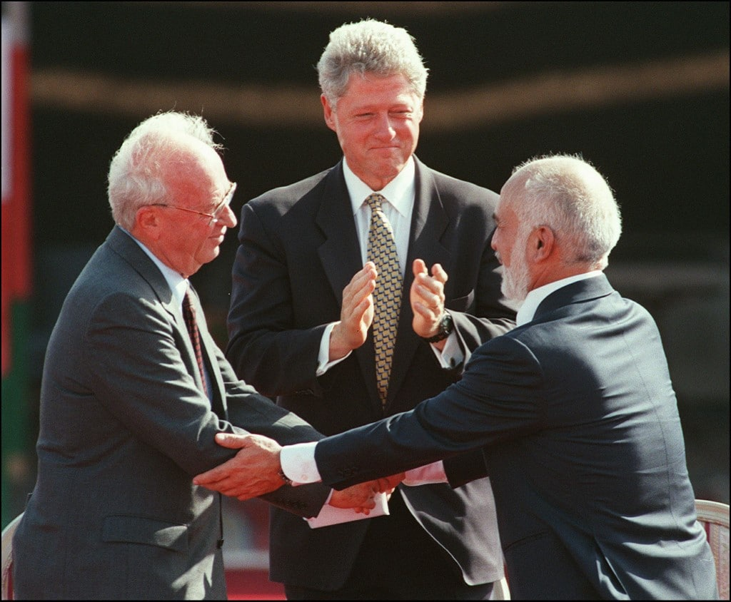 King Hussein of Jordan and Israeli Prime Minister Yitzhak Rabin shake hands on 26 October 1994, in the presence of US President Bill Clinton