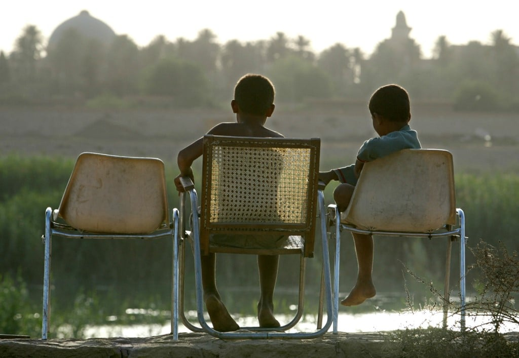 Two Iraqi children sit at sunset on the banks of the Tigris river in Iraq