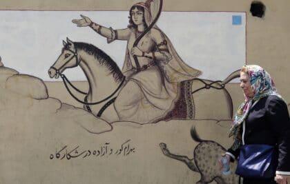 woman passes murales
