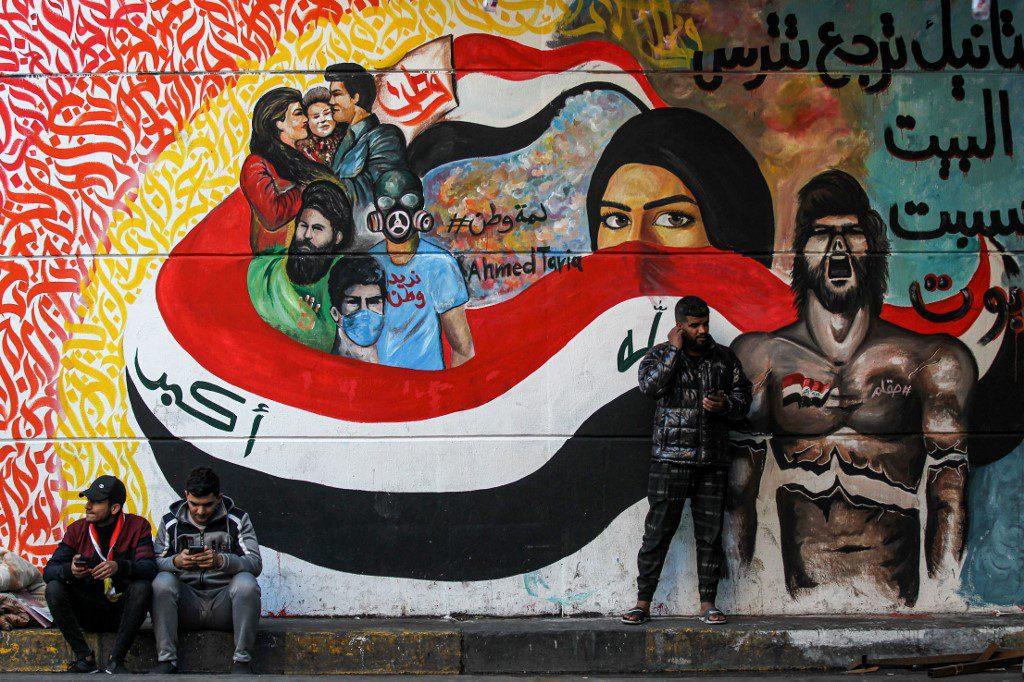 Iraqi men sit by a graffiti mural