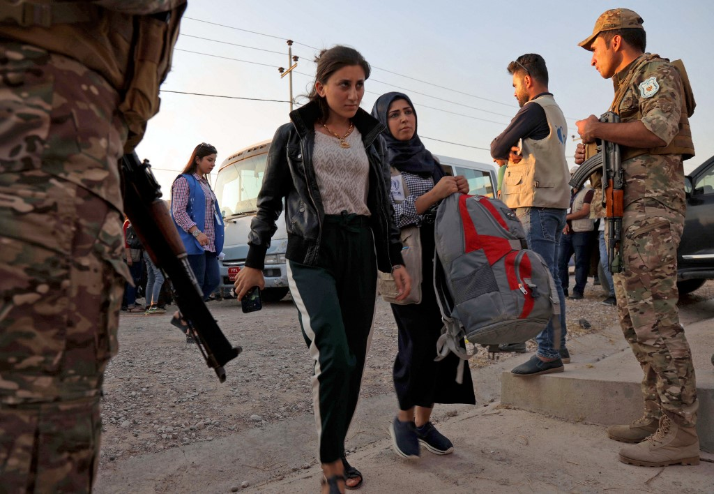 Two women walk after disembarking from a minibus transporting Syrians fleeing the ongoing Turkish military operation in northeastern Syria