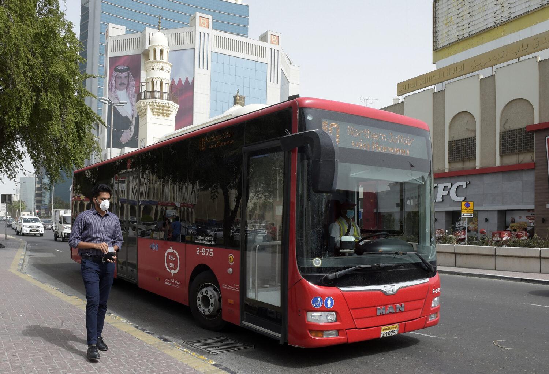 رجل يرتدي قناع بجوار حافلة سياحية في البحرين