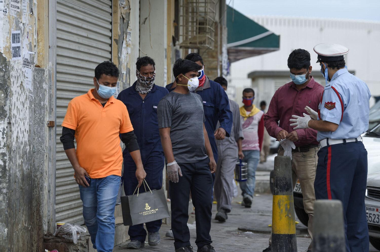 يوعز ضابط شرطة بحريني للعمال الأجانب ، في السوق القديمة للعاصمة المنامة.