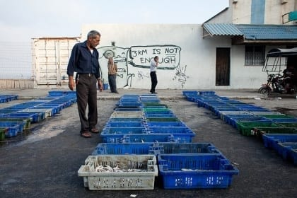 Fisherman in Gaza with text protesting against the sea blockade on a wall