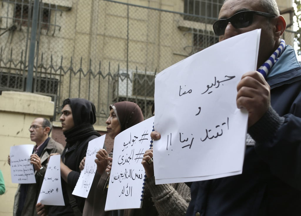 """Mourners hold slogans at a vigil for Italian student Giulio Regeni, found dead with signs of torture after having gone missing on January 25, 2016. Demonstrators gathered in front of the Italian embassy in Cairo, Egypt, on Saturday, February 6, 2016. The posters read, """"Giulio is one of us and was killed like us"""" and """"Giulio and El Gendi the same pain the same date."""" Photo Amr Nabil/AP."""