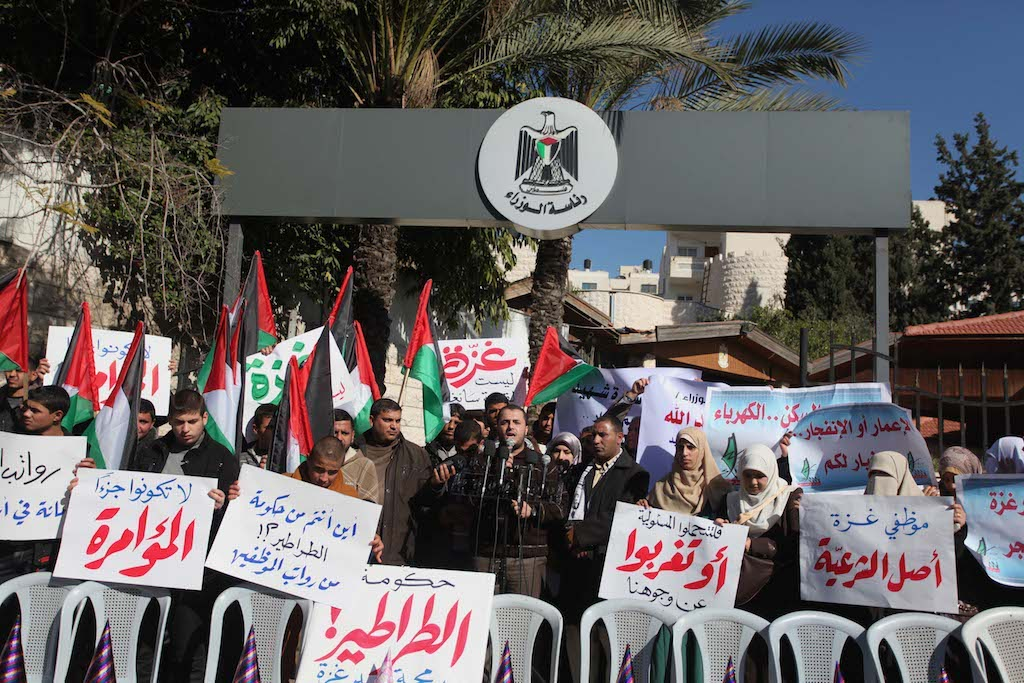 December 31, 2014 - Gaza City, Gaza Strip, Palestinian Territories: Palestinians hold posters during a rally organized by employees of former Palestinian government demanding their salaries to be paid, in front of the headquarters of the Council of Ministers. Some 40,000 civil servants employed by the Hamas government stopped receiving salaries soon after the formation of the Palestinian unity government in June. (Ashraf Amra/APAImages/Polaris)