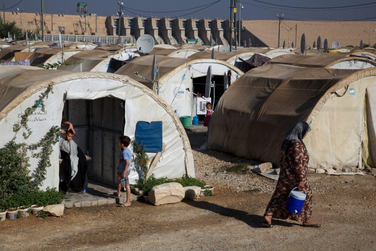 صبي يبلغ من العمر 3 سنوات يحصل على قصة شعر في صالون حلاقة مؤقت أقيم في إحدى الخيام في مخيم اللاجئين السوريين