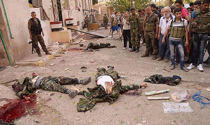 Syrian Army soldiers stand next to apparent rebel bombers dressed in military gear after they were shot near the scene where multiple bombs explosions hit the center of Aleppo