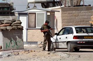 Israeli soldier checking the identity of a Palestinian driver at a military checkpoint in Bethlehem, May 2002 Israeli occupation