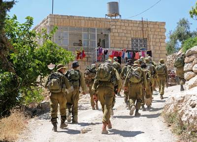 Israeli soldiers walk past a Palestinian house in the hills of Halhoul, near Hebron, in a military operation to find three kidnapped Israeli settlers, 22 June 2014 / Photo eyevine/HH