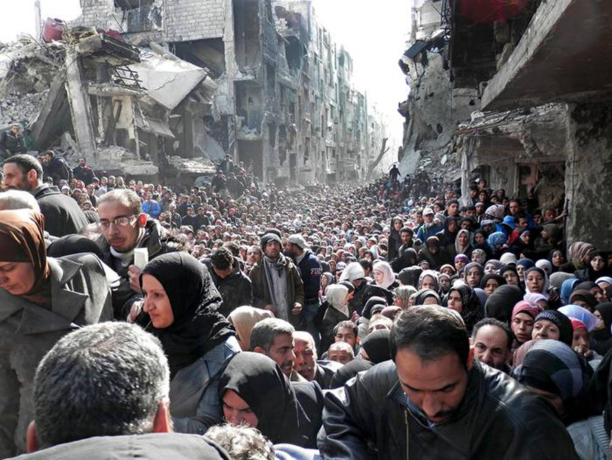 Residents of the besieged Yarmouk camp south of Damascus wait to receive food aid distributed by the UN