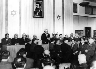 David Ben-Gurion reading out the Declaration of Independence of the State of Israel on 14 May 1948, beneath a portrait of Theodor Herzl, father of modern political Zionism