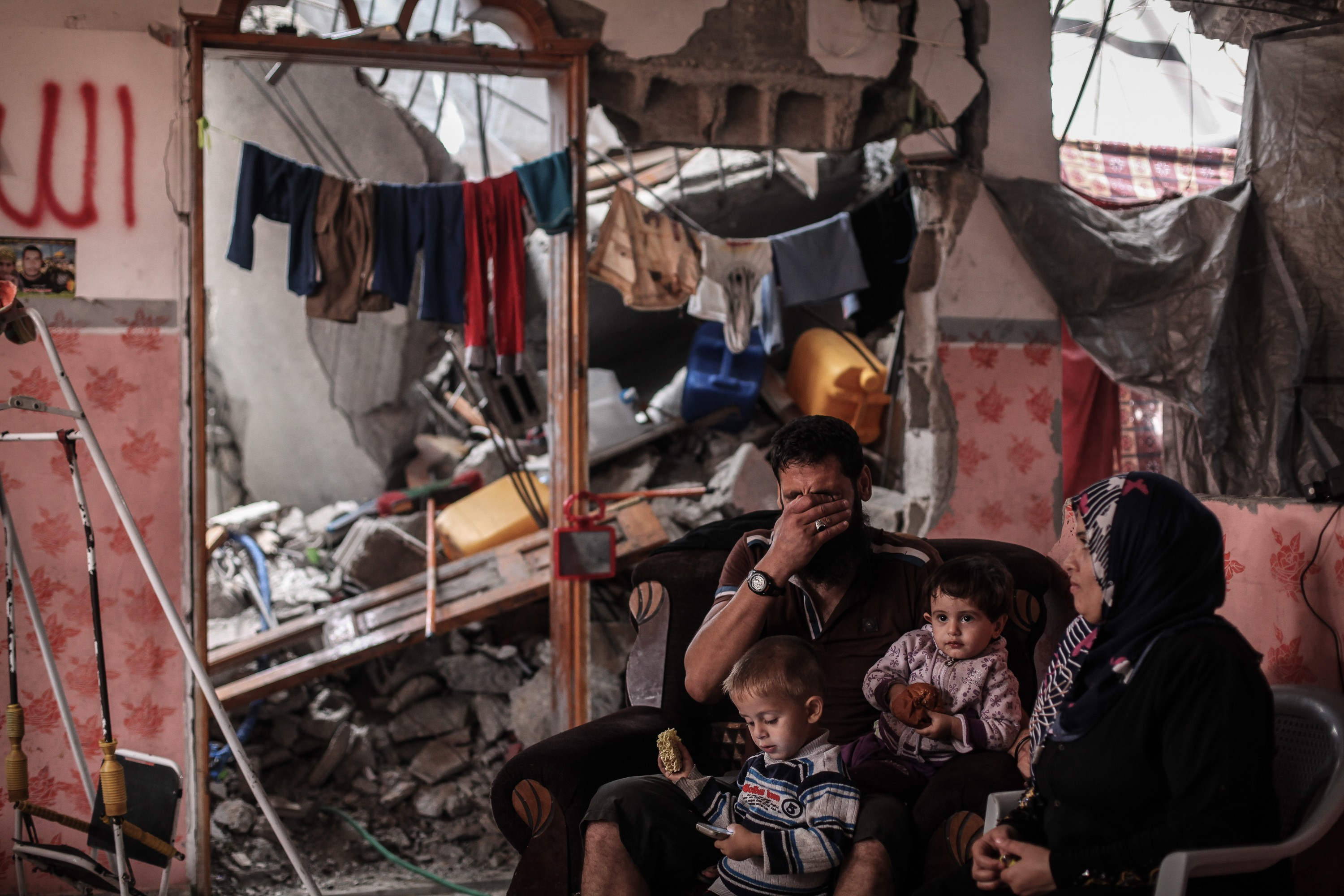 Madi Hasanein and his family are sitting in what remains of their house which was destroyed during the war, Gaza City, October 2014 / Photo Corbis