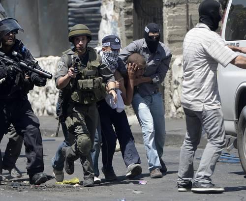 Israeli secret policemen detain a Palestinian boy during a demonstration staged after Friday Prayer in Jerusalem, 1 August 2014 / Photo Anadolu Agency