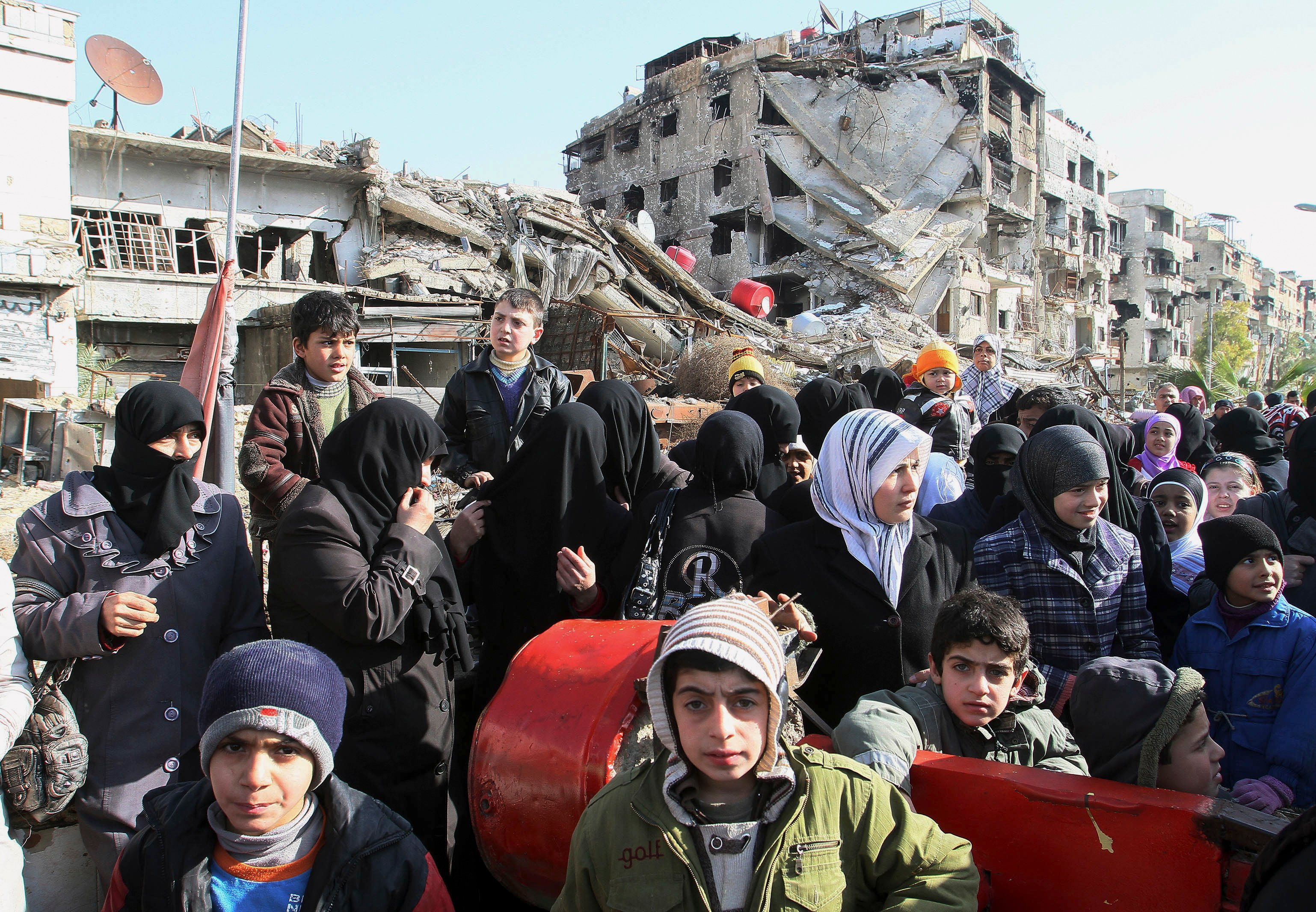 Hundreds of Syrians wait in line at a military checkpoint