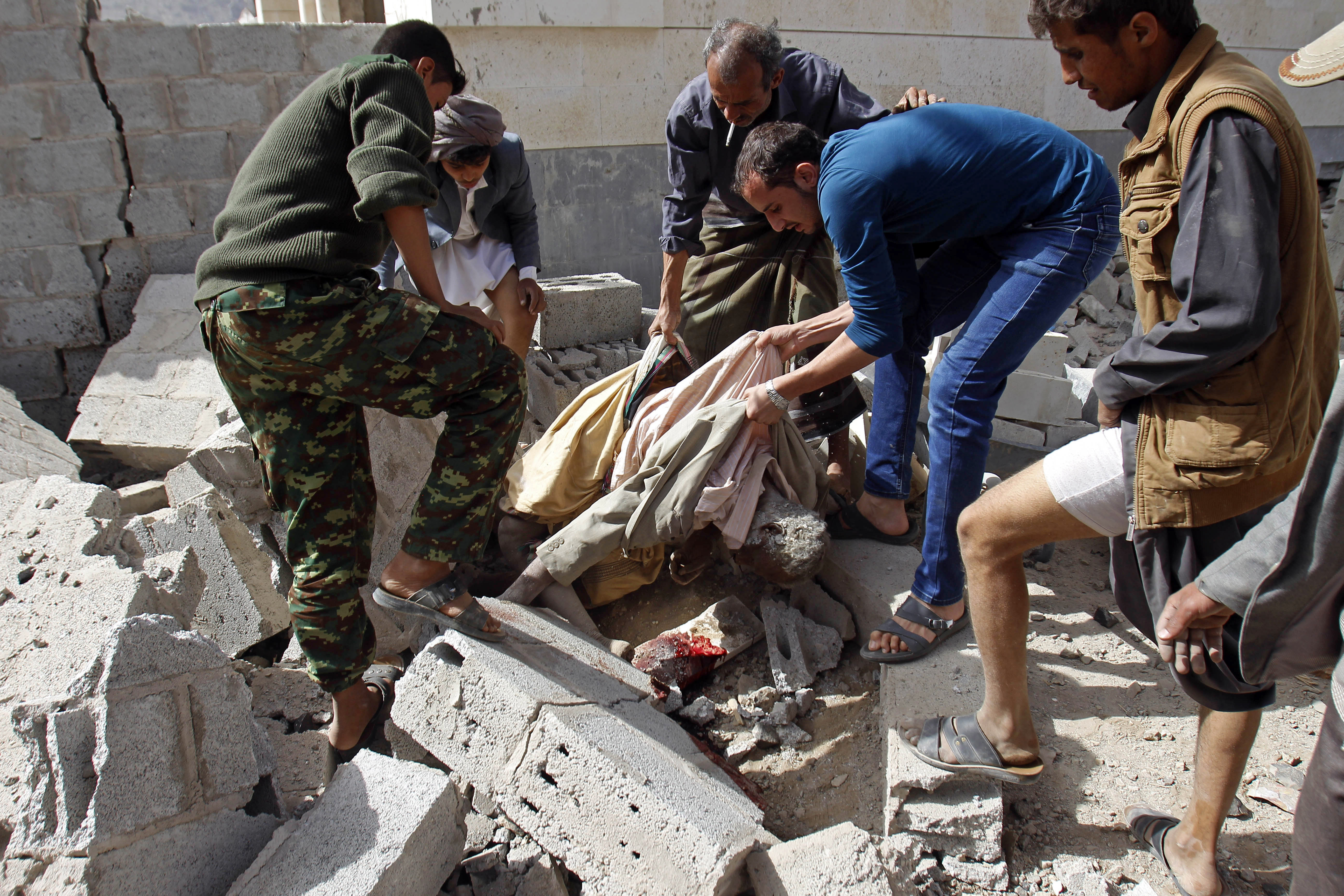 People carry the body of a man killed in a Saudi-led airstrike against Iran-allied Shiite rebels, known as Houthis, that hit a site of a weapons cache in Yemen's capital, Sanaa, Monday, April 20, 2015. The strikes on Yemen's rebel-held capital on Monday caused massive explosions that shattered windows, sent residents scrambling for shelter and killed a local TV presenter. (AP Photo/Hani Mohammed)
