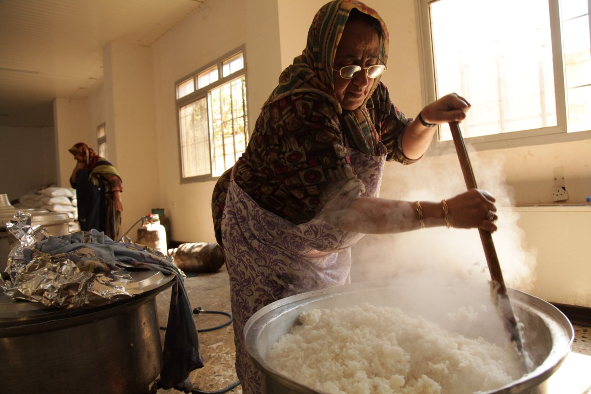 """Wedding chef Zainab Mohammad stirs a cauldron of rice, destined for rebel fighters on Libya's frontlines. A team of more than 30 volunteers, led by a 5 Star hotel chef, are helping to cook up to three meals a day, in an old Naval baracks in Benghazi. Boy scouts pack the food into individual portions and lorries deliver them to the frontlines. Zeenab, an Egyptian born mother of eight, who used to cater wealthy family weddings, said: """"The fighters are all our children. I wanted to be here with all my heart."""""""