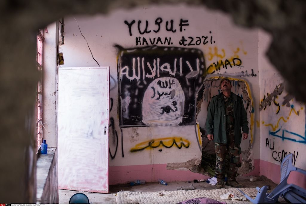 A Kurdish Peshmerga fighter gives a tour of Islamic State hideouts in the newly liberated city of Sinjar. Yazidi members of the Kurdish forces have already covered over some of the graffiti with their own. January 2016, Sinjar, Iraq. Photo Laurence Geia/SIPA.