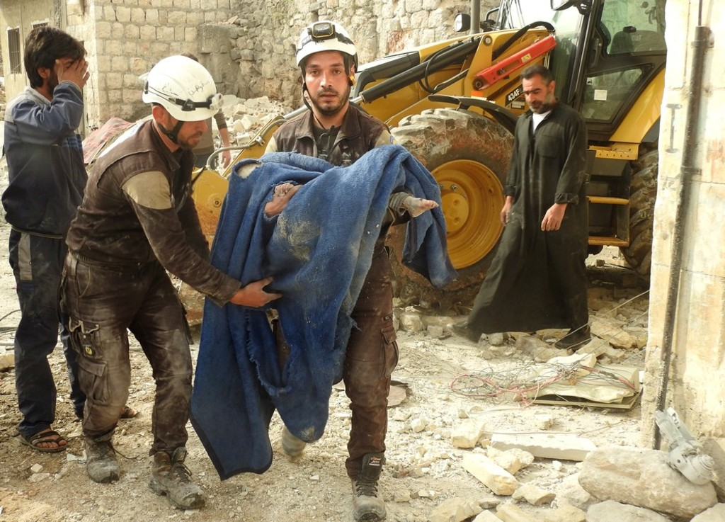 Syrian-rescue-team-member-carries-the-dead-body-of-a-kid