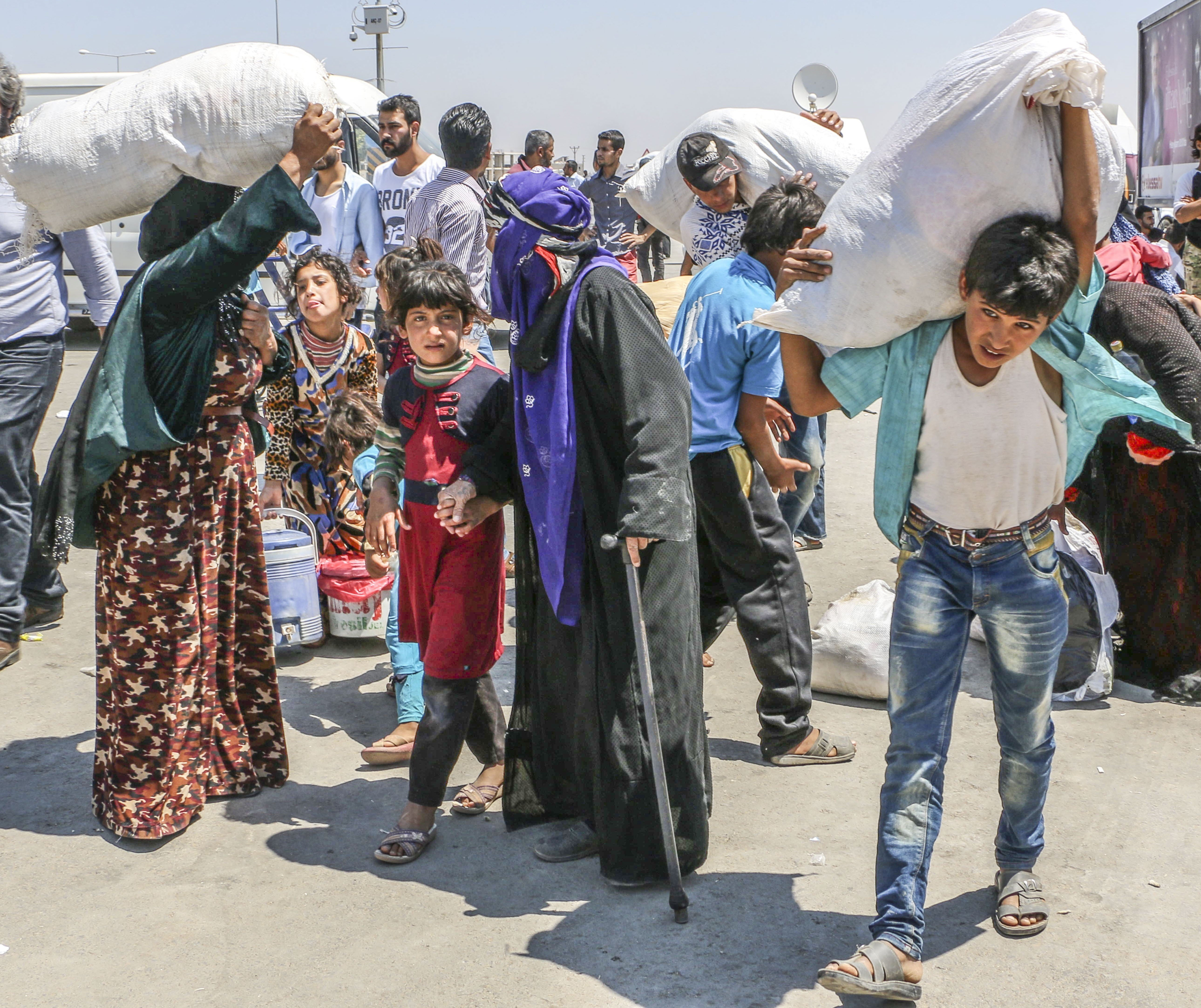 Syrian refugees return to the Syrian town of Tal Abyad from Turkey