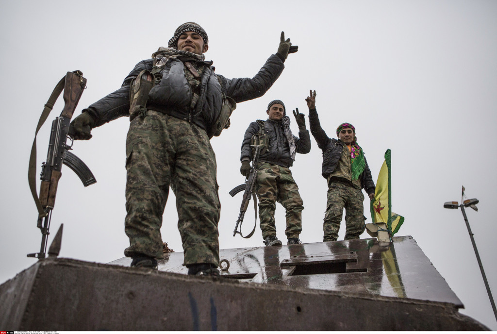 Kurdish YPG fighters stand on an armored truck confiscated from the Islamic State in Kobane, Syria, 30 January 2015. Photo